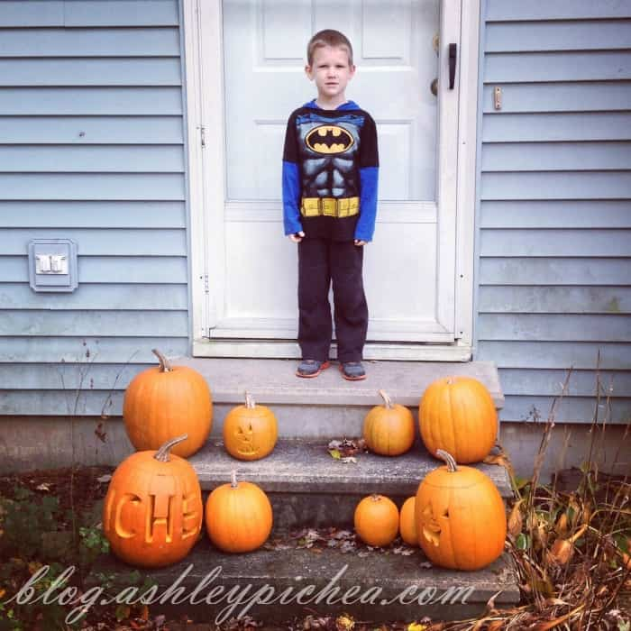 Pumpkin Carving with Kids - David with the carved pumpkins on the front porch