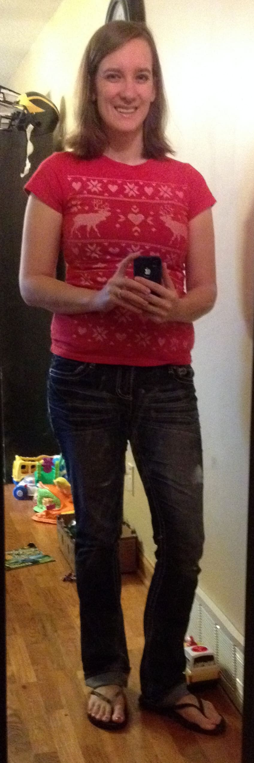 red Christmas-y tshirt, jeans, black flip flops