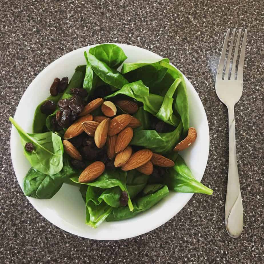 a bowl full of spinach, almonds, and raisins is an easy meal idea for better nutrition during pregnancy