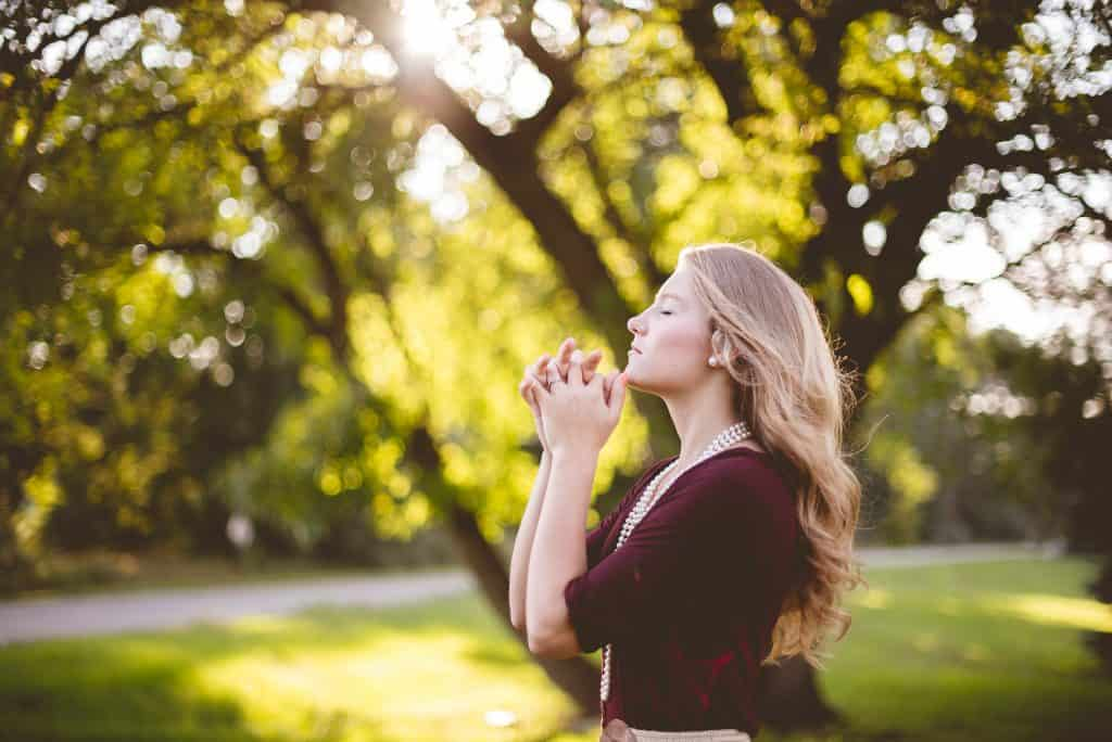 blonde woman praying outside