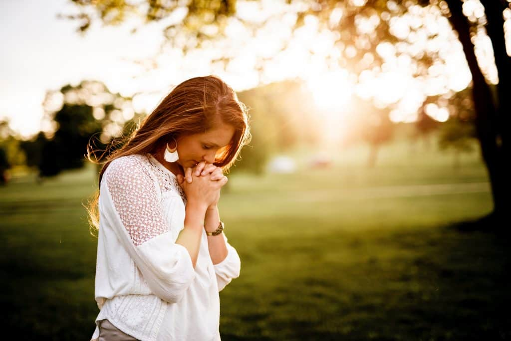 woman in white shirt praying outside at golden hour