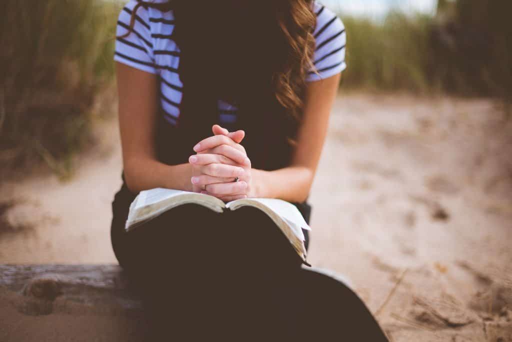 woman praying with hands folded over open bible - no face shown